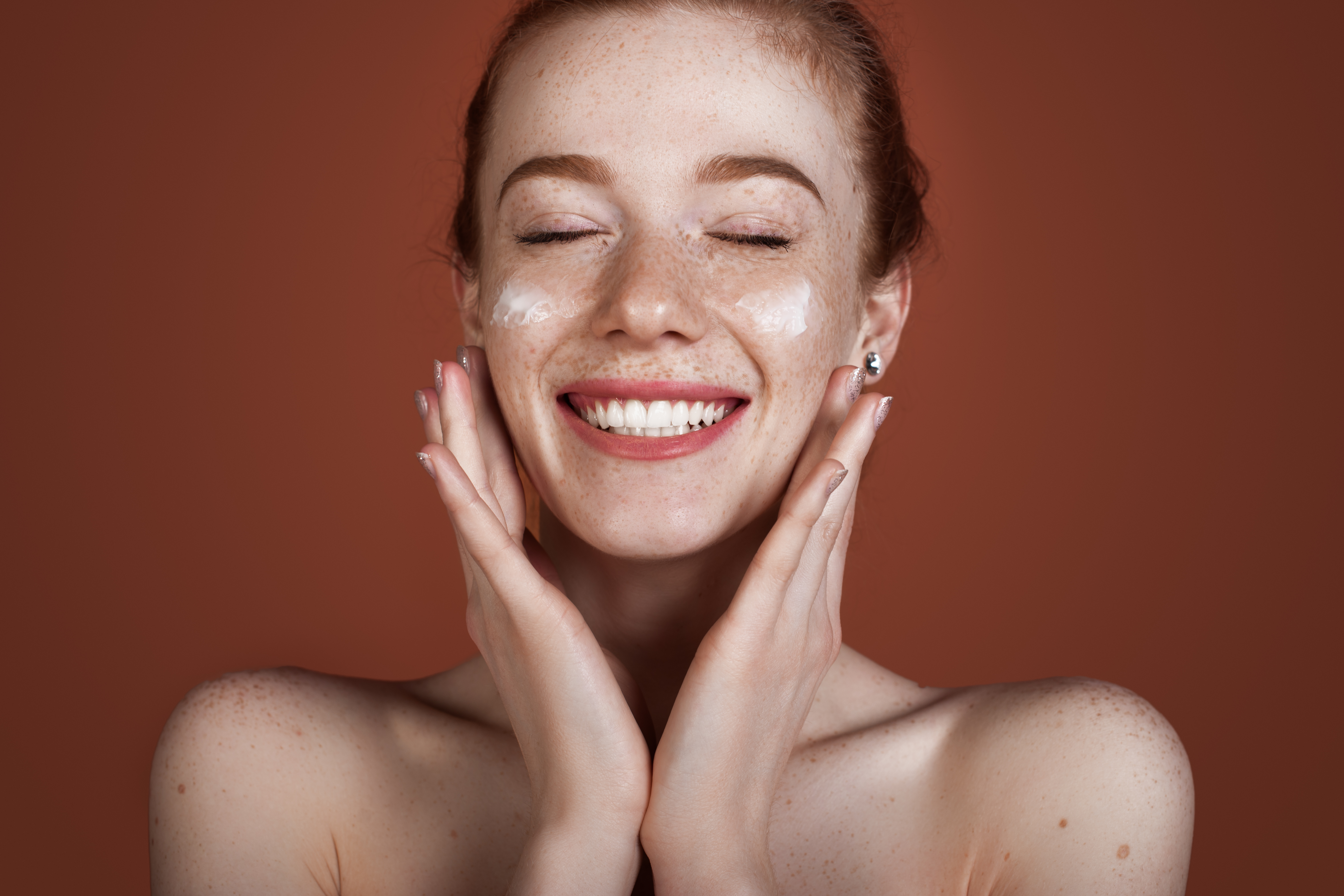 Smiling caucasian ginger lady with freckles applying anti aging cream on face and smile posing with naked shoulders on red studio wall
